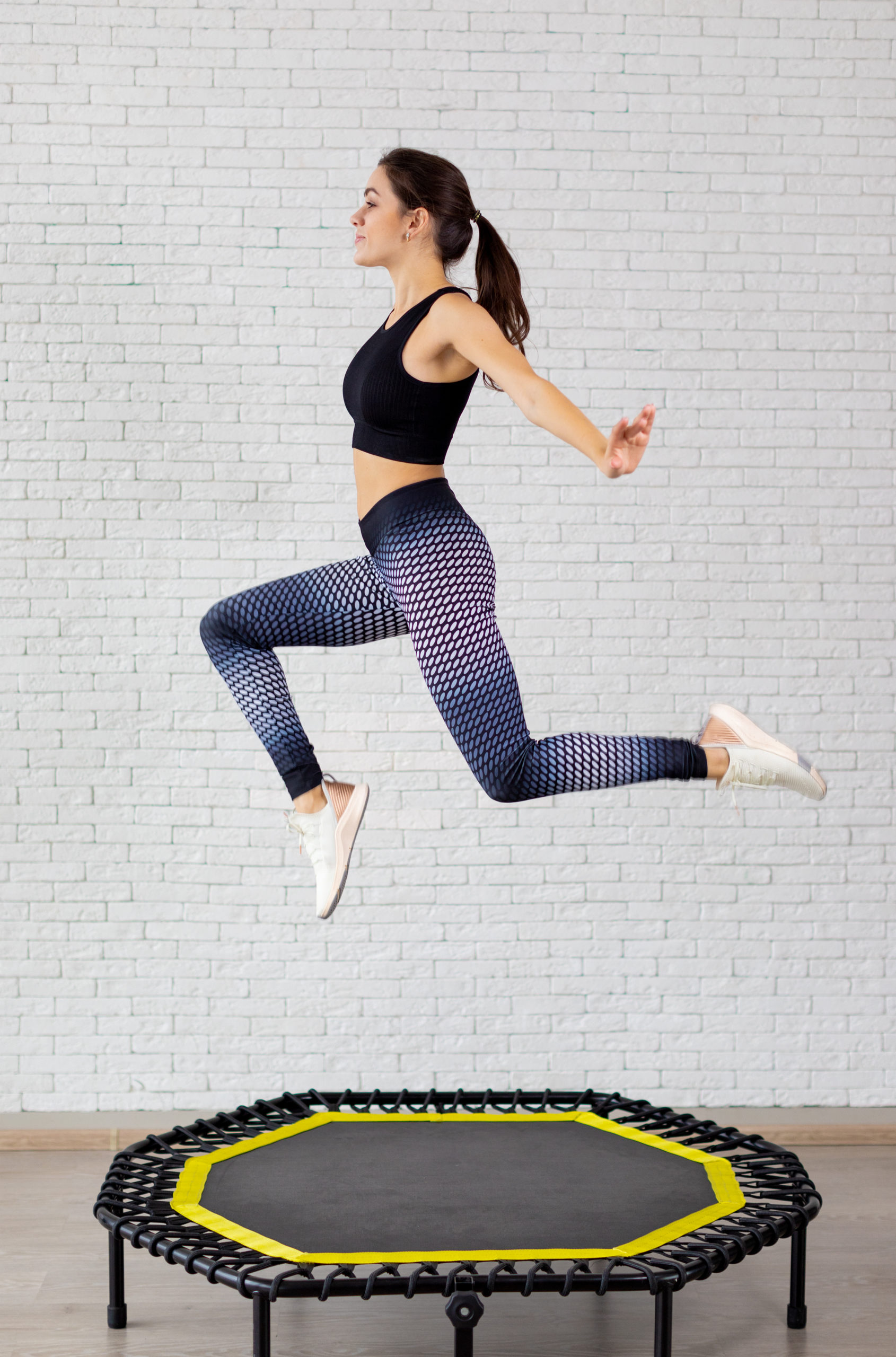 Relaxed woman jumping on trampoline.young fitness girl trains on a mini trampoline in the Studio